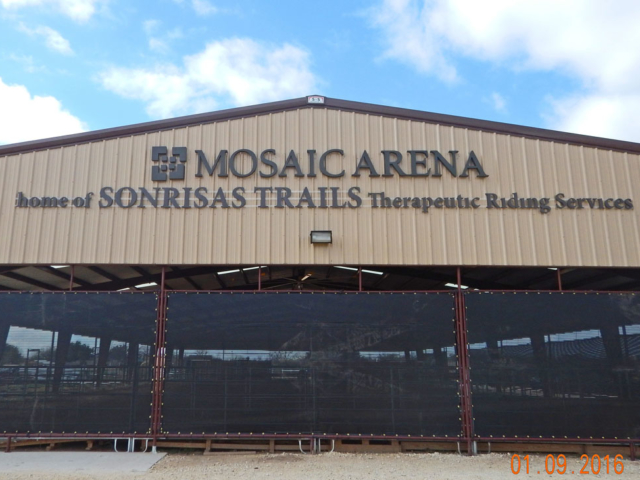 Mosaic arena therapeutic riding facilities utilize windscreens to keep participants and horses more comfortable because of less blowing dust, chilling winds and less hot summer sun.